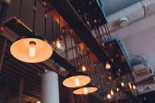 Retro Copper Hanging Lamp With Orange Light Bulb.