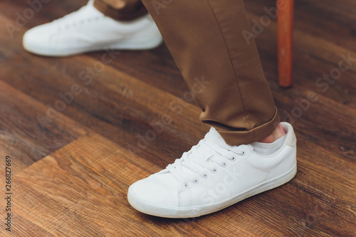 White sneakers,lower half, legs, on wooden boards. Canvas Print
