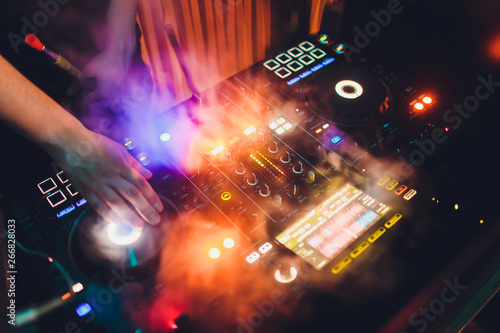 Disc Jockey DJ Entertainment with EDM Dance Music Mixer CD Player in Night Club with Lighting and Smoke Effect in Holiday. - 266828033