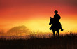 canvas print picture - cowboy riding in the hills at sunset