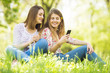 canvas print picture - Two young women sitting outdoors and using phone