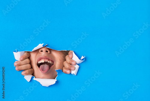 Young boy poking his tongue through a hole torn in paper background Fototapeta