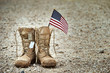 canvas print picture - Old military combat boots with dog tags and a small American flag. Rocky gravel background with copy space. Memorial Day, Veterans day, sacrifice concept.