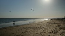 Two Kitesurfers And Some People At Sunset On The Beach