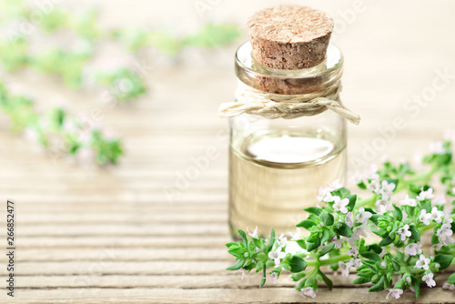 Thyme essential oil in the glass bottle, with thyme flowers. Canvas-taulu