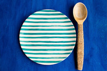 Empty Plate And Wooden Spoon On Blue Background