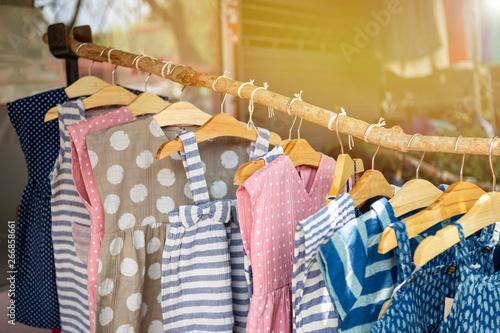 Obraz Kids's fashion, cute little girl dress hanging on wooden stick over blurred cloth shop background - fototapety do salonu