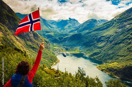 Tourist over Geirangerfjord with norwegian flag Canvas Print