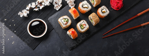 Tuinposter Sushi bar Set of sushi and maki rolls with branch of white flowers on stone table