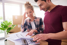 Worried Couple Examining Expenses After Moving Into New House