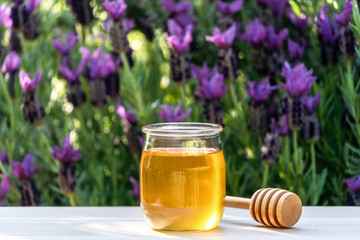 Jar of organic floral honey with a wooden drizzle against lavender background . Outdoor.