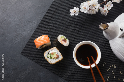 Autocollant pour porte Sushi bar Set of sushi and maki rolls with branch of white flowers and teapot on stone table