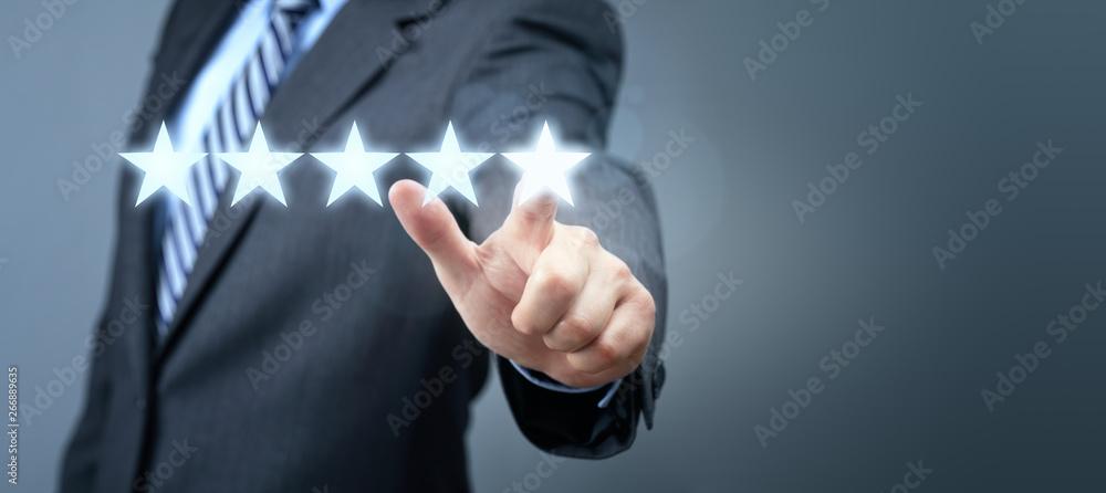 Fototapeta Businessman pointing to five star service rating symbol