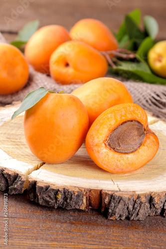 A lot of fresh, ripe apricot in a bag on a brown wooden background Canvas Print