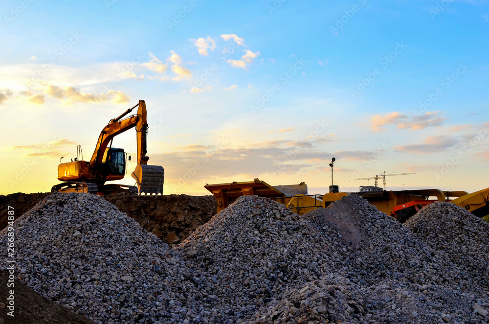 Fototapety, obrazy: Heavy excavator bucket working in quarry on a background of sunset and blue sky. Mobile jaw stone crusher by the construction site. Crushing old concrete wastes and subsequent cement production