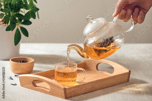 Valokuvatapetti A hand pouring tea from glass teapot on wooden serving tray