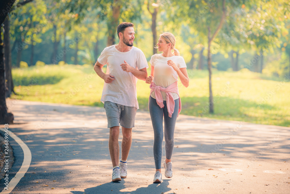 Fototapeta Portrait of Young couple running in the park at sunset. Concept sport and love. Warm tone.