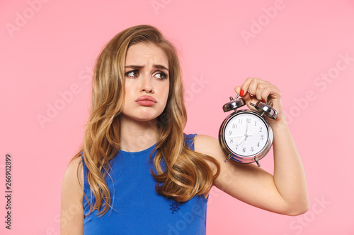 Obraz Displeased young pretty woman posing isolated over pink wall background holding alarm clock. - fototapety do salonu