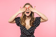 Happy young pretty woman posing isolated over pink wall background covering eyes.
