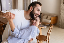 Photo Of Laughing Brunette Couple In Love Smiling While Hugging Together In Apartment