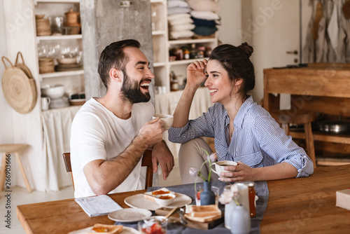Fotografiet Image of modern brunette couple eating breakfast together while sitting at table