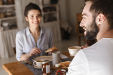 Image Of Positive Brunette Couple Eating Together At Table While Having Breakfast In Apartment