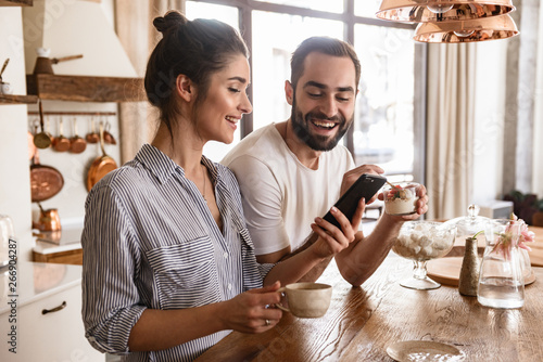 Photographie Photo of european brunette couple drinking coffee and using cell phone during br