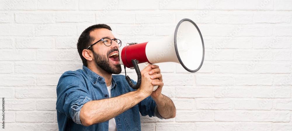 Fototapeta Handsome man with beard over white brick wall shouting through a megaphone