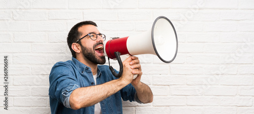 Handsome man with beard over white brick wall shouting through a megaphone Canvas Print