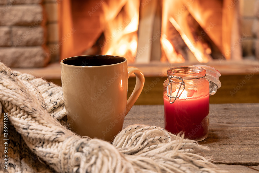 Fototapety, obrazy: Big mug with hot tea, and a candle , wool scarf, near cozy fireplace, hygge, home sweet home.