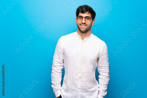 Fotografiet  Young man over isolated blue wall with glasses and happy