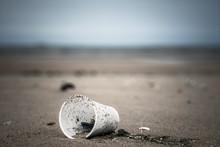 Verre En Plastique Trainant Sur Le Sable