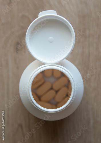 Foto op Plexiglas Tabletten in the bottle on a wood background.