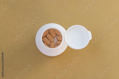 Foto op Plexiglas Tabletten in the bottle on a yellow background.