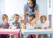 Group of nursery babies toddlers eating healthy food lunch break together with kindergartener