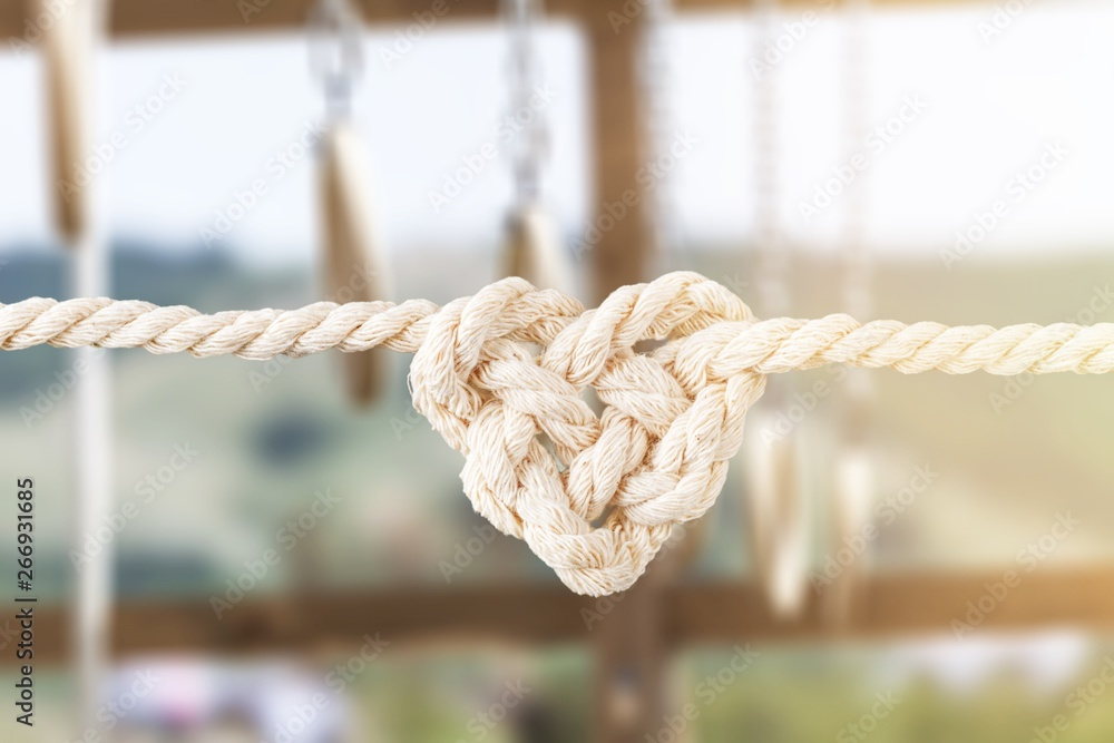Fototapety, obrazy: White rope in heart shape knot on background. Love concept.