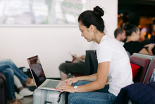 Young Female Passenger Using Laptop Computer At Airport While Waiting For Her Flight