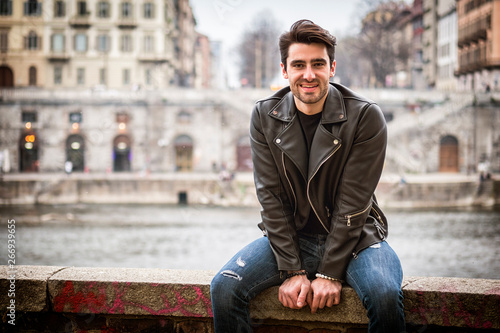 Fotografia  One handsome young man in urban setting in modern city, smiling, standing, weari