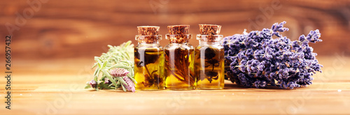 Fototapeta essential lavender oil in a glass bottle on a background of fresh flowers obraz
