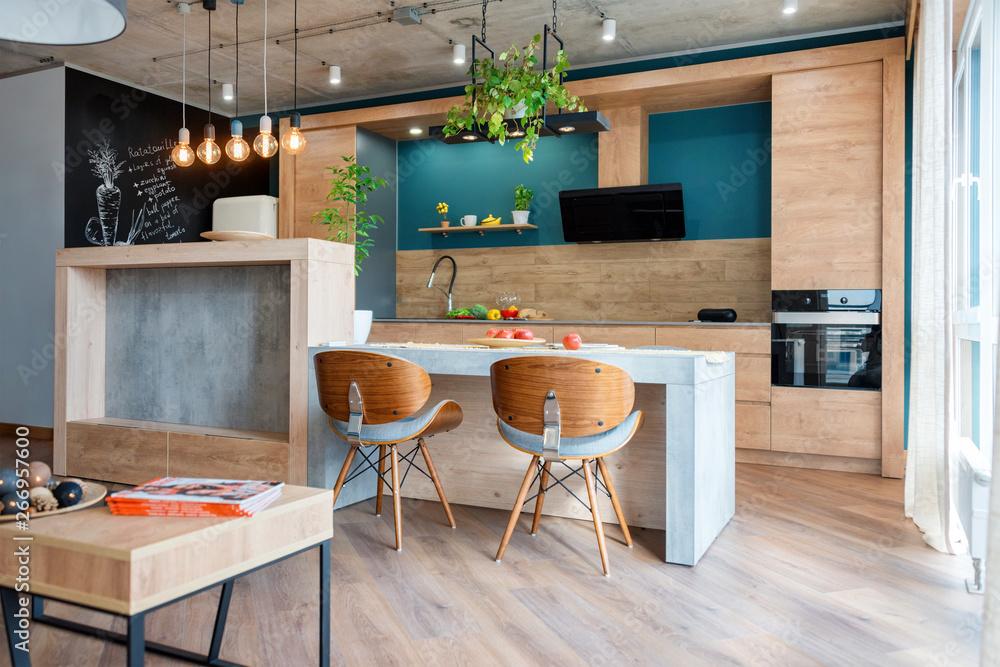 Fototapeta Modern furniture in luxury kitchen. Minimalist scandinavian interior in loft apartment with wooden furniture, lamps, concrete elements and plants