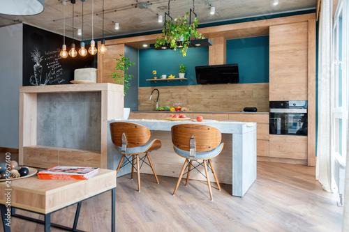 Fototapeta Modern furniture in luxury kitchen. Minimalist scandinavian interior in loft apartment with wooden furniture, lamps, concrete elements and plants obraz