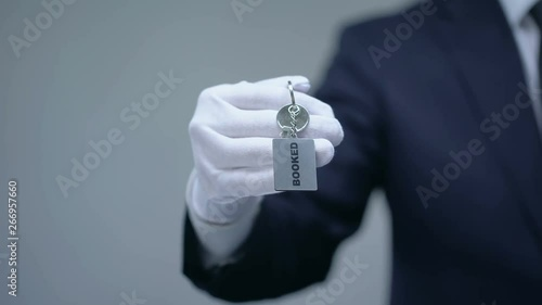 Booked word on keychain in receptionist hand, luxury hotel services, closeup