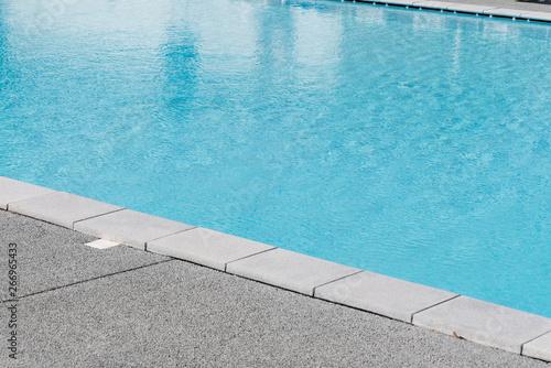 Edge of swimming pool with blue water Fototapeta