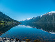 An endless chain of mountains reflecting itself in a calm water of Eidfjord. Taller parts of the mountains are partially covered with snow. Sunny and bight weather, clear blue sky. Romantic landscape