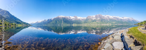 Obraz An endless chain of mountains reflecting itself in a calm water of Eidfjord. Taller parts of the mountains are partially covered with snow. Sunny and bight weather, clear blue sky. Romantic landscape - fototapety do salonu