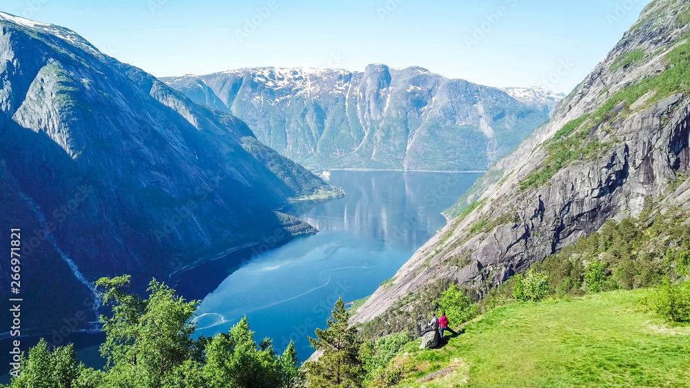 Fototapety, obrazy: A couple standing on the meadow with a majestic view on Eidfjord from Kjeasen, Norway. Slopes of the mountains are overgrown with lush green grass. Water has dark blue color. Sunny and clear day