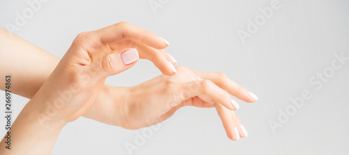 Close-up of women's hands with gentle Nude French nails manicure on a light background with space for text. Long wide banner.