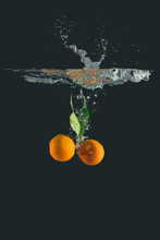 Mandarin Oranges With Leaves Falling Into Water