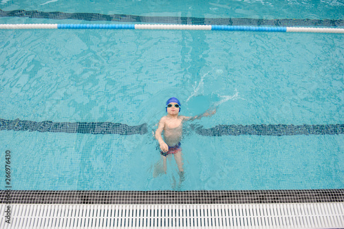 Photo top view of a 7-year boy swimming backstroke in a swimming pool