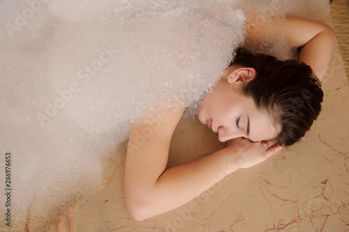 top view of a young woman in white foam relaxing in a hamam Canvas Print
